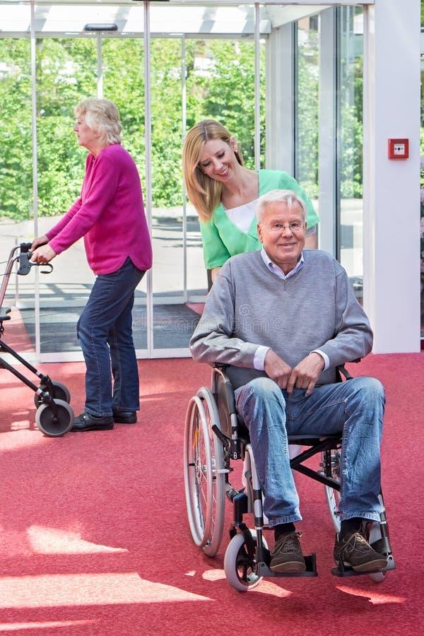 Sjuksköterska Pushing Senior Man i rullstol i lobby arkivfoto