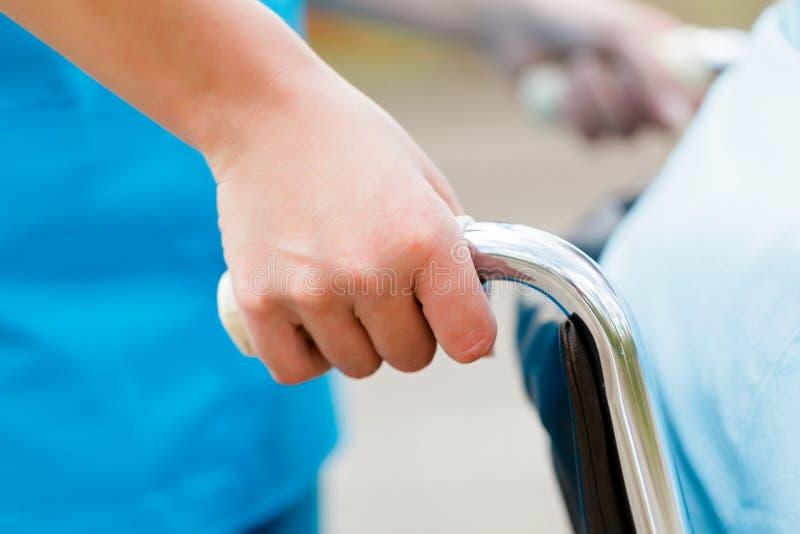 Sjuksköterska Pushing Wheelchair fotografering för bildbyråer