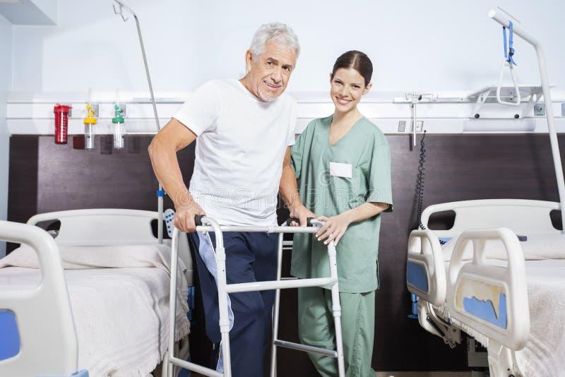Sjuksköterska With Senior Man som använder Walker In Rehab Center royaltyfria bilder