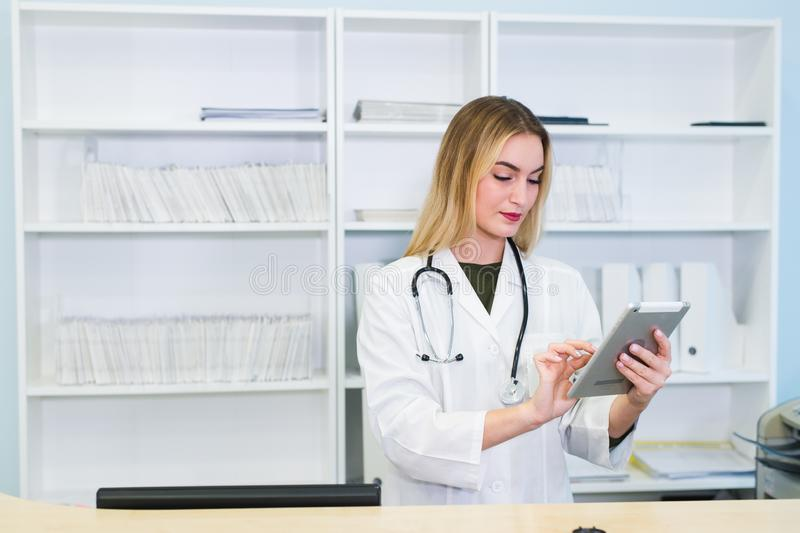 Sjuksköterska som använder den digitala minnestavlan i mottagande av det moderna sjukhuset arkivbild