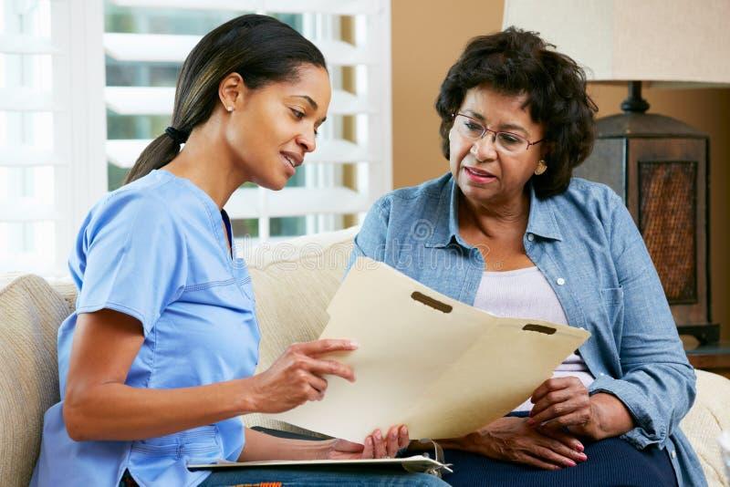 Sjuksköterska som diskuterar rekord med hög kvinnlig tålmodig under hem royaltyfri bild