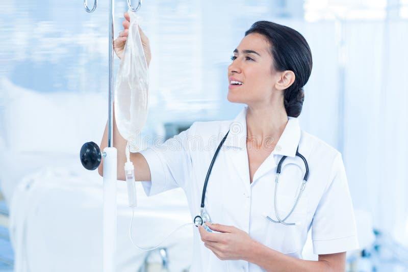 Sjuksköterska som förbinder en dropp arkivfoto