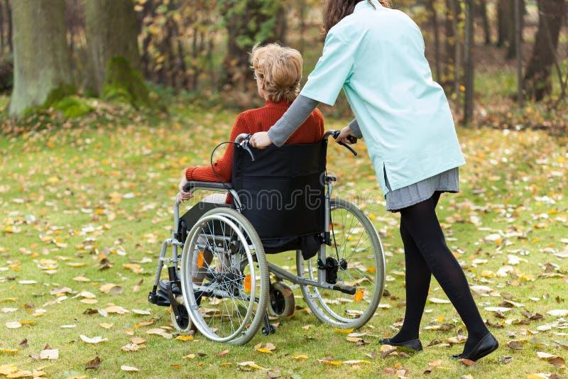Sjuksköterska som går med den rörelsehindrade damen royaltyfri fotografi
