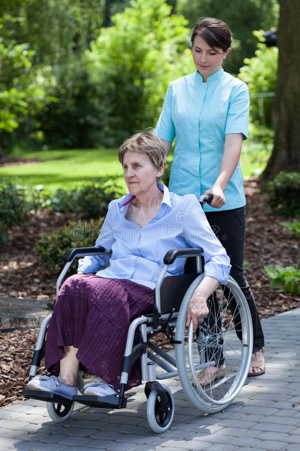 Sjuksköterska som går med den rörelsehindrade damen arkivbilder