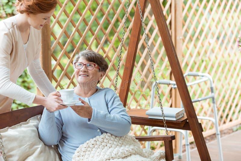 Sjuksköterska som ger koppen kaffe arkivbild