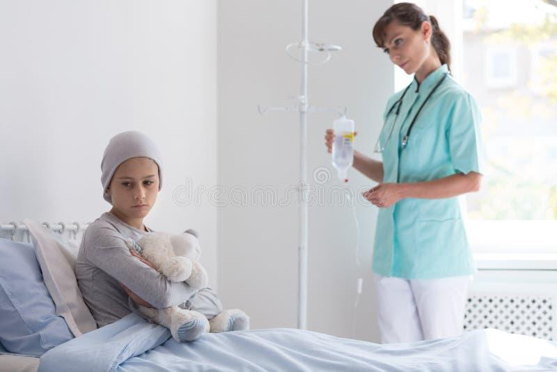 Sjuksköterska som ger läkarbehandlingen till flickan med cancer som kramar nallebjörnen i klosterhärbärgen royaltyfri foto