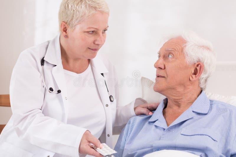 Sjuksköterska som ger preventivpillerar till den höga patienten arkivfoto