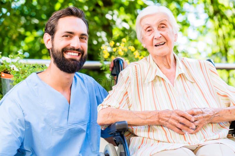 Sjuksköterska som har pratstund med den höga kvinnan i vårdhem royaltyfri foto