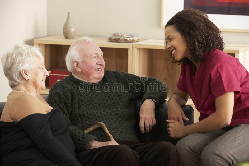 Sjuksköterska som hemma besöker höga par royaltyfri foto