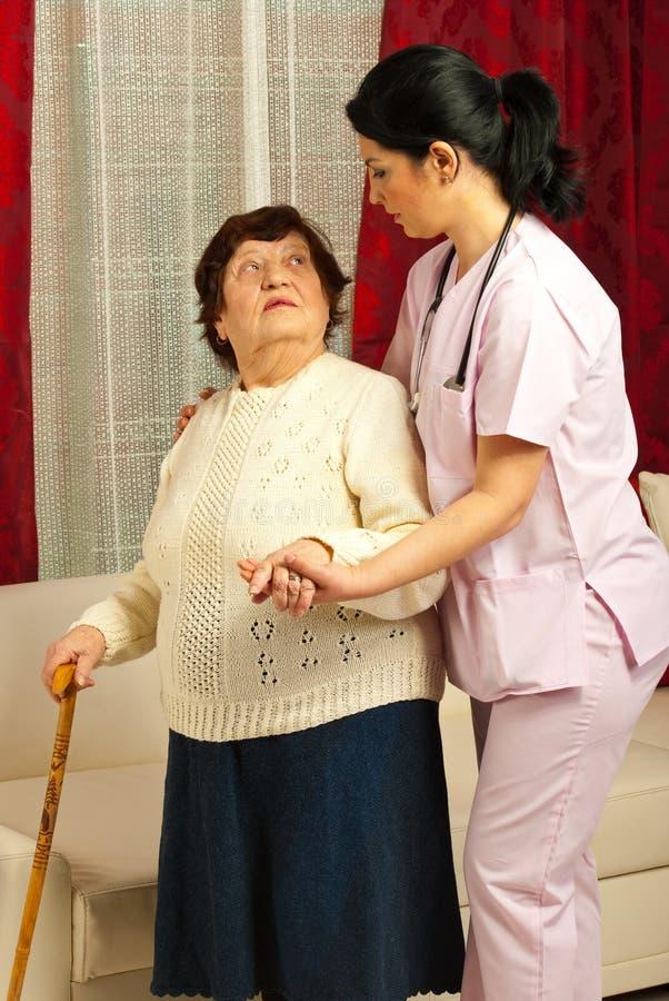 Sjuksköterska som hjälper den gammalare kvinnautgångspunkten arkivfoton