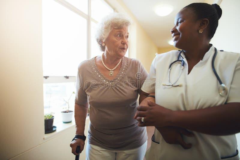 Sjuksköterska som hjälper den höga kvinnliga patienten för att gå arkivbilder
