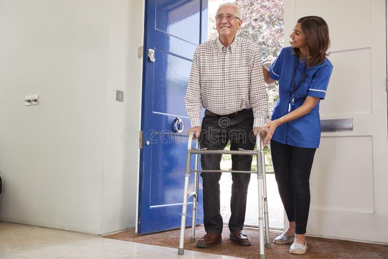 Sjuksköterska som hjälper den höga mannen som hemma använder en gå ram fotografering för bildbyråer