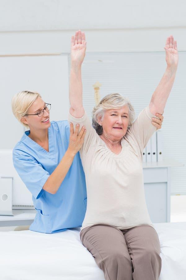 Sjuksköterska som hjälper den kvinnliga patienten, i att öva royaltyfria foton