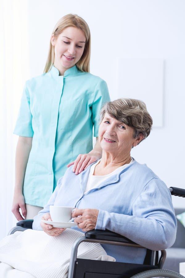Sjuksköterska som hjälper den rörelsehindrade höga kvinnan arkivfoto