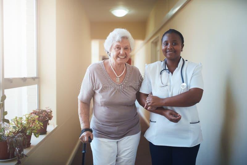Sjuksköterska som hjälper en hög patient för att gå royaltyfri fotografi