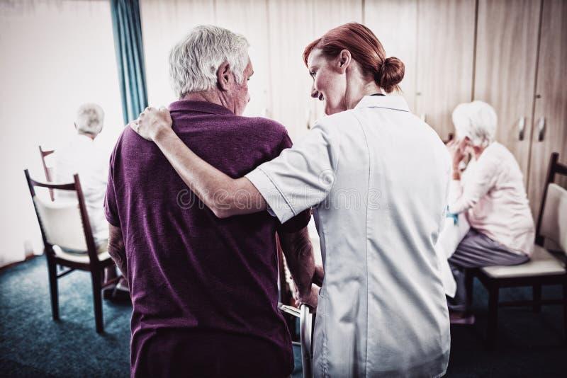 Sjuksköterska som hjälper en pensionär som använder en fotgängare arkivbilder