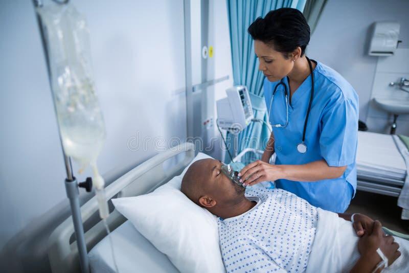 Sjuksköterska som justerar syremaskeringen på tålmodig mun royaltyfri bild