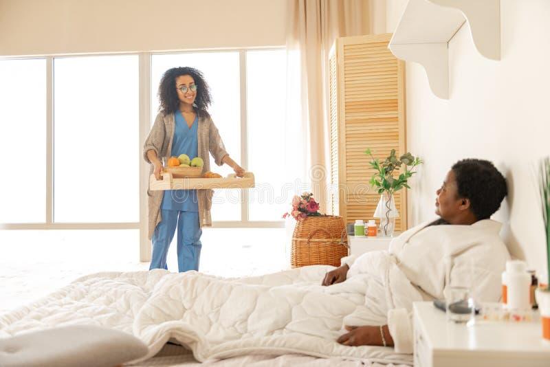 Sjuksk?terska som kommer med magasinet med frukosten f?r patient efter kirurgi arkivfoton