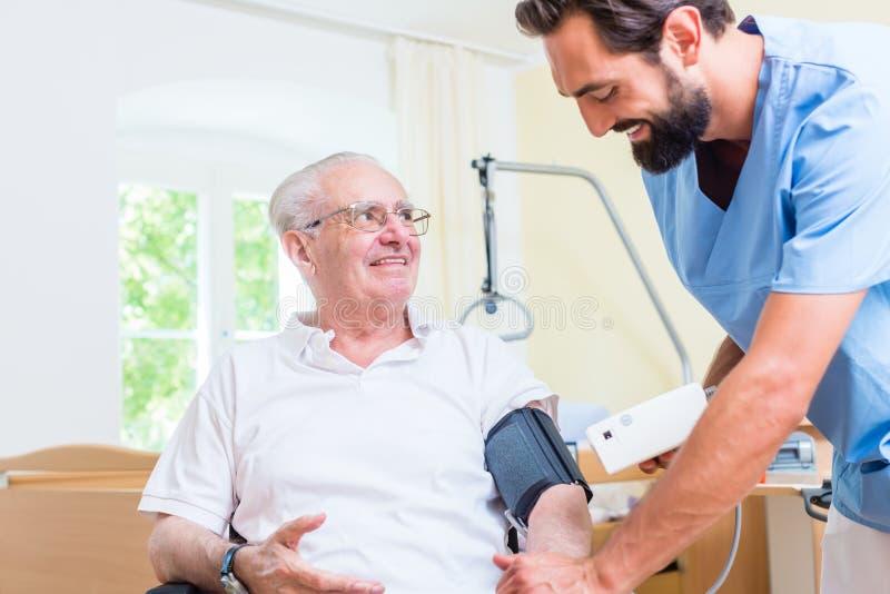 Sjuksköterska som mäter blodtryck av den höga patienten royaltyfri fotografi