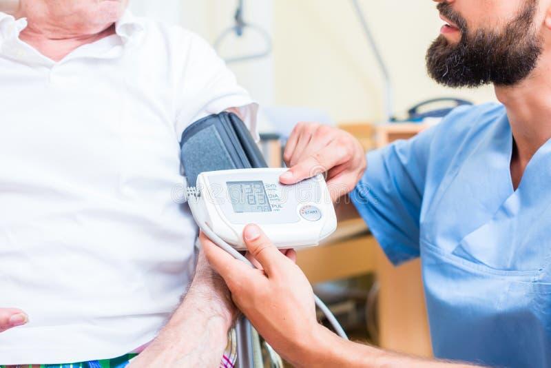 Sjuksköterska som mäter blodtryck av den höga patienten royaltyfria bilder