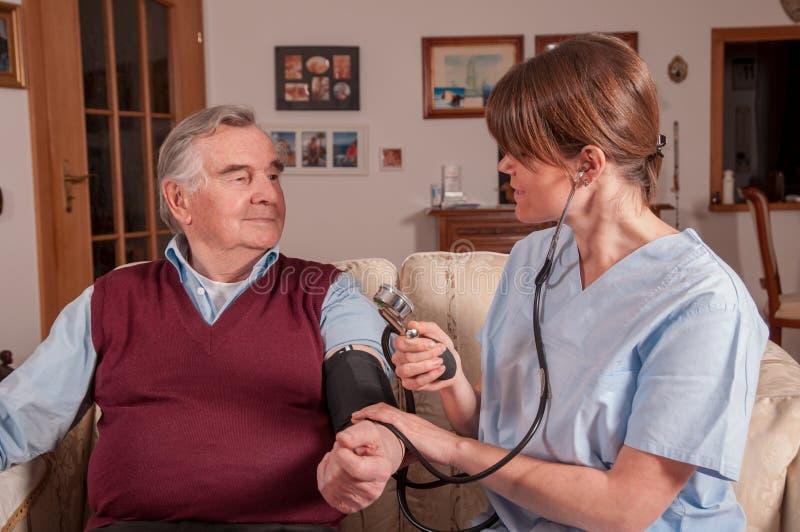 Sjuksköterska som mäter blodtryck med sphygmomanometeren royaltyfria foton