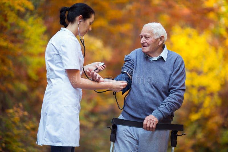 Sjuksköterska som mäter gammalt tålmodigt blodtryck för ` s royaltyfri bild
