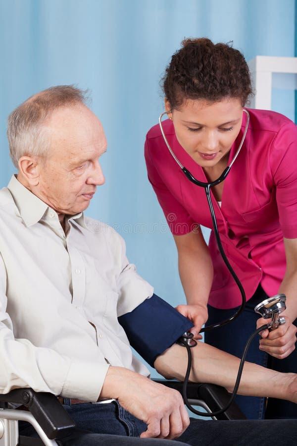 Sjuksköterska som mäter patients tryck royaltyfria foton