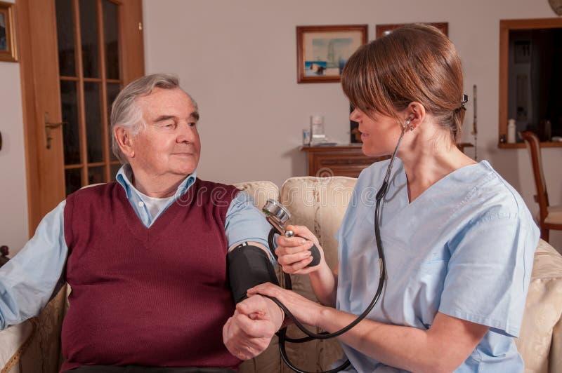 Sjuksköterska som mäter senior' s-blodtryck arkivbild