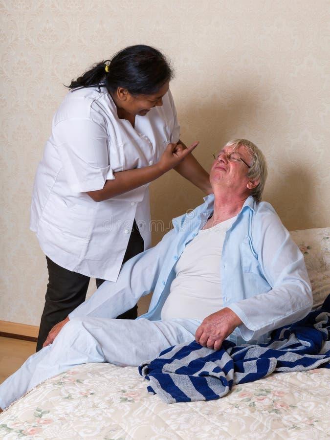Sjuksköterska som ropar på den äldre mannen royaltyfri bild