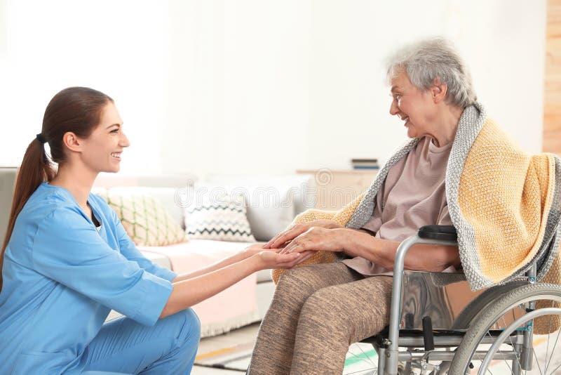 Sjuksköterska som rymmer äldre kvinnas händer Hjälpa högt folk royaltyfria foton
