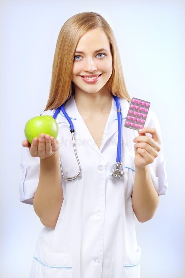 Sjuksköterska som rymmer ett äpple och pills royaltyfri bild