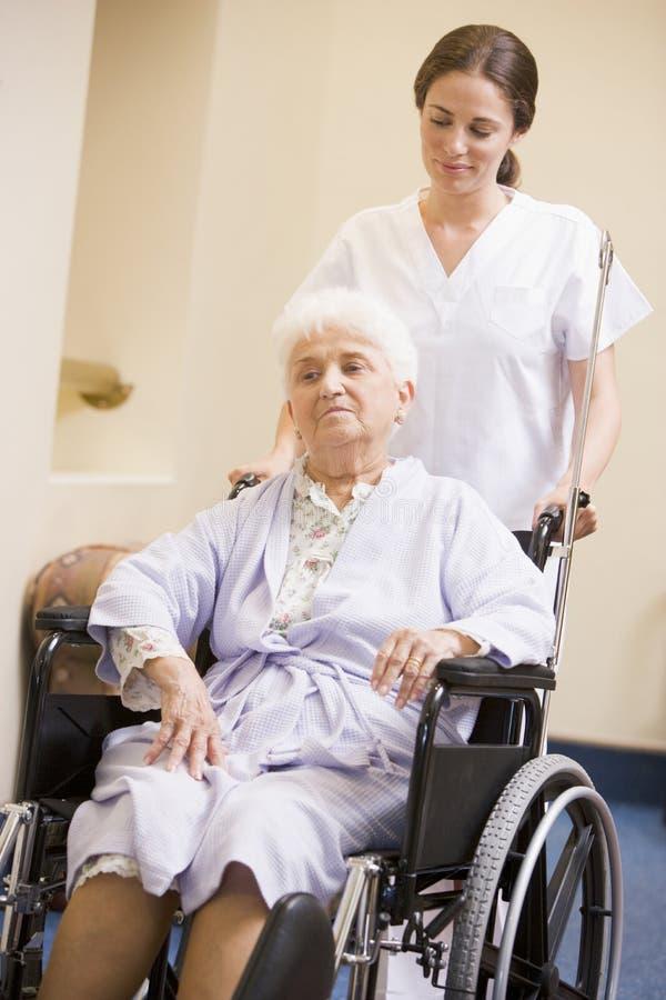 sjuksköterska som skjuter den höga rullstolkvinnan royaltyfri bild