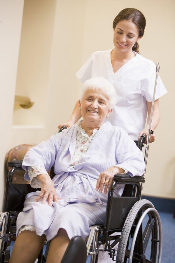 sjuksköterska som skjuter den höga rullstolkvinnan royaltyfri fotografi