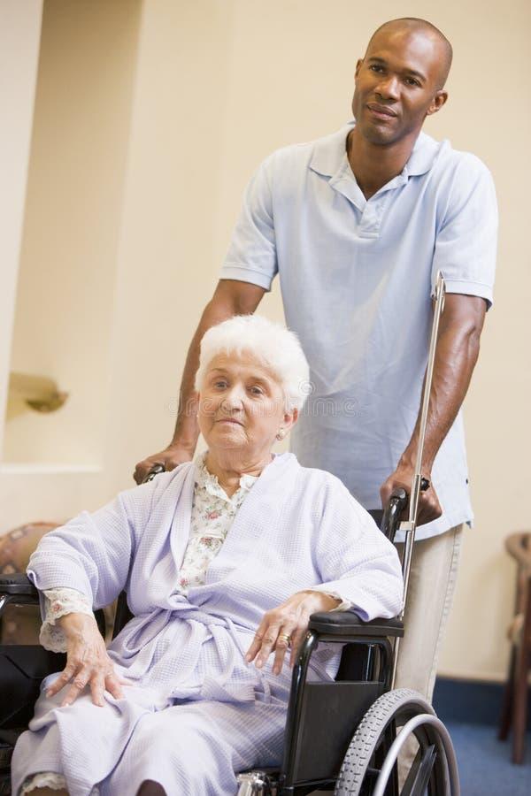 sjuksköterska som skjuter den höga rullstolkvinnan arkivbild