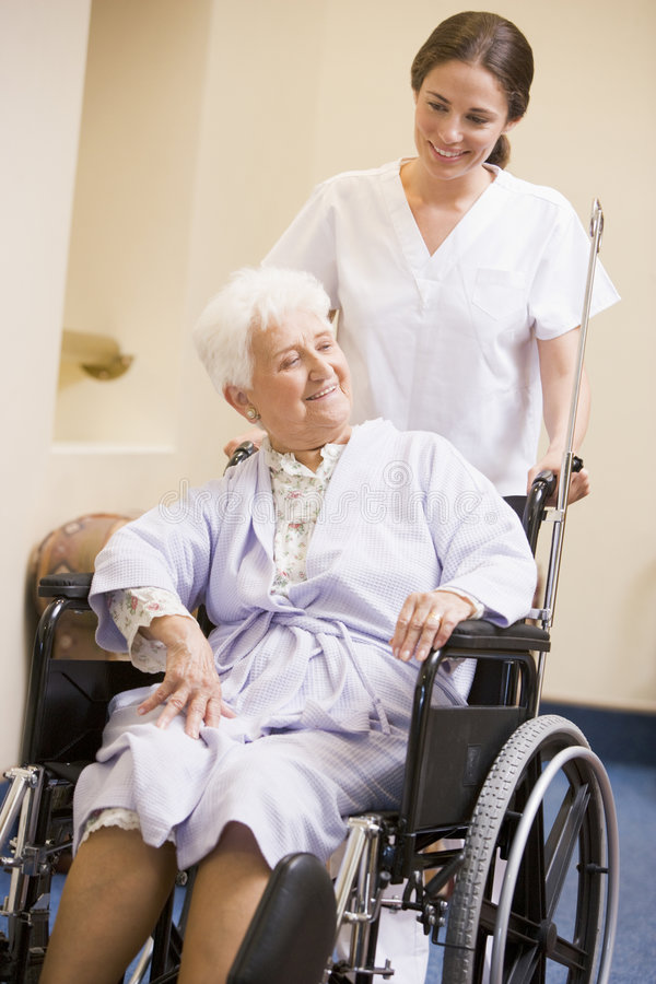 sjuksköterska som skjuter rullstolkvinnan royaltyfri bild