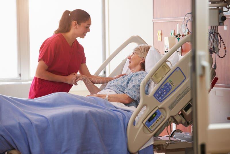 Sjuksköterska som talar till hög kvinnlig tålmodig i sjukhussäng arkivfoton