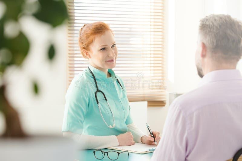 Sjuksköterska som talar till tålmodign royaltyfri bild