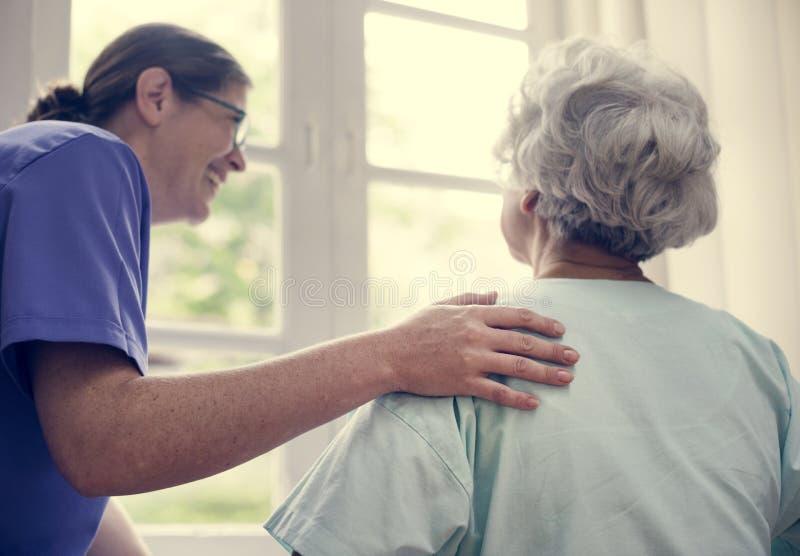 Sjuksköterska som tar omsorg av en gammal kvinna fotografering för bildbyråer