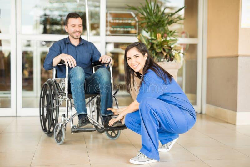 Sjuksköterska som tar patienten för en promenad royaltyfri bild