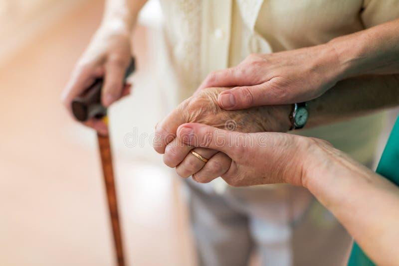 Sjuksköterska som tröstar hennes äldre patient, genom att rymma hennes händer royaltyfri foto