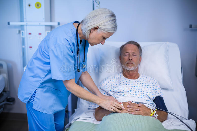 Sjuksköterska som undersöker en patient royaltyfri fotografi