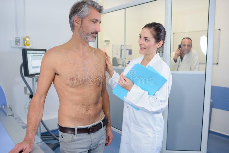 Sjuksköterska som uppmuntrar den manliga patienten royaltyfria bilder