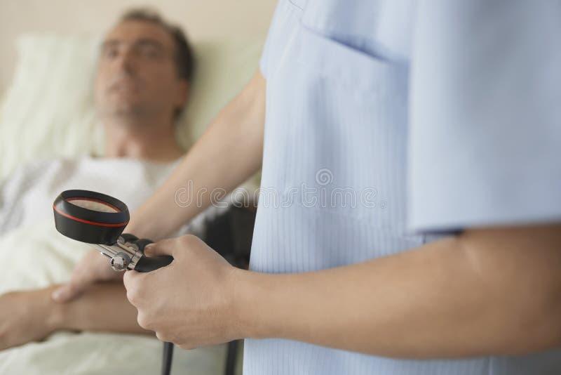 Sjuksköterska Taking Blood Pressure och puls av patienten arkivfoton