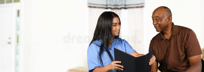 Sjuksköterska Taking Care av pensionären arkivbilder