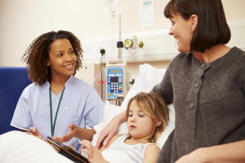 Sjuksköterska Talking To Mother och dotter i sjukhussäng arkivfoto
