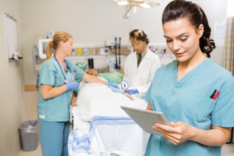 Sjuksköterska Using Digital Tablet medan doktor And royaltyfria bilder