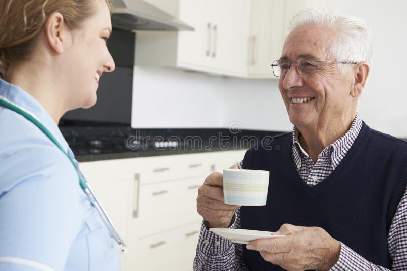SjuksköterskaChatting With Senior man under hem- besök royaltyfri foto
