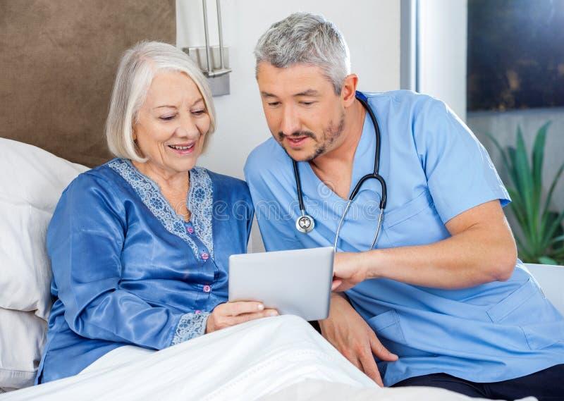 SjuksköterskaDiscussing Over Digital minnestavla med pensionären royaltyfria bilder