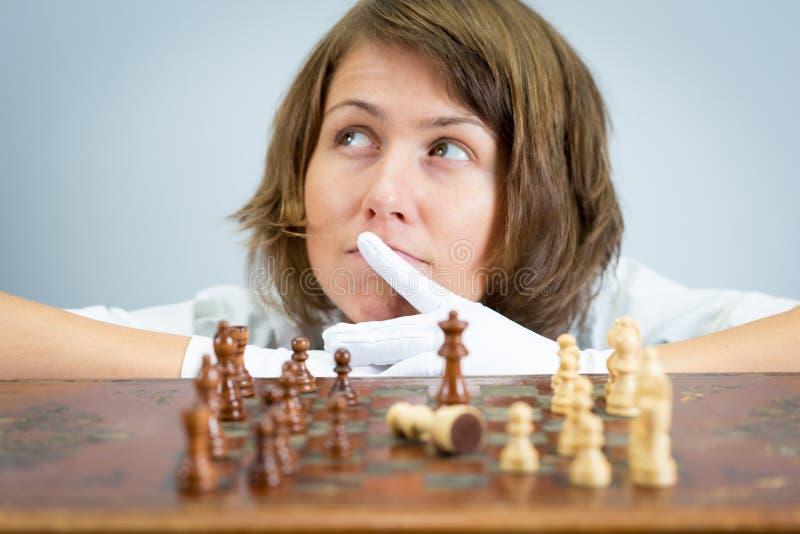 Sjuksköterskadoktor för ung kvinna som spelar schackmatta tänkande lekstycken för schack arkivbilder