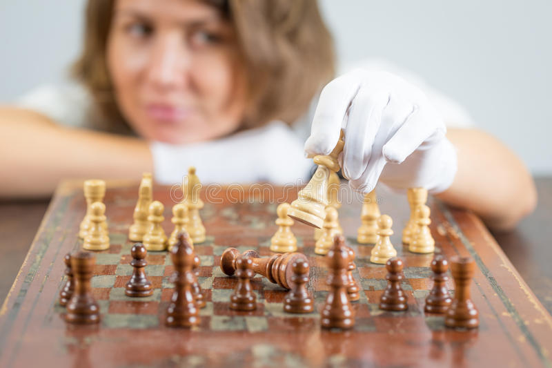Sjuksköterskadoktor för ung kvinna som spelar schackmatta tänkande lekstycken för schack arkivbild